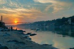 Ansicht der Brücke des Flusses Ganga und Ram Jhulas bei Sonnenuntergang Stockbilder