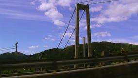 Ansicht an der enormen Brücke im grünen Hügelland Berge bedeckten grünes Waldwasser Baum auf dem Gebiet stock footage
