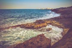 Ansicht der felsigen Küste, der schäumenden Wellen des Meeres und der Stadt im Abstand bei Sonnenuntergang Stockfoto