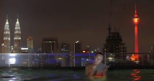 Ansicht der Frau im Swimmingpool auf dem Wolkenkratzerdach unter Verwendung der Tablette gegen Nachtstadtlandschaft Kuala Lumpur, stock video footage