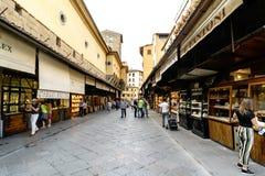 : Ansicht der Geschäfte gelegen auf die Seiten der Brücke auf dem Arno, genannt ` ` Ponte Vecchio mit dem Leutegehen lizenzfreie stockbilder