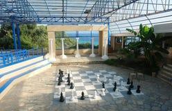 Ansicht der Halle mit großen Schachfiguren und die Ansicht des blauen Meeres in einem griechischen Hotel stockfotografie
