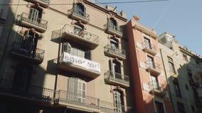 Ansicht der Hausmauer mit Balkonen, wellenartig bewegender katalanischer Flagge und Plakat Demokratie stock footage