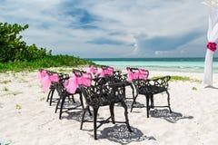 Ansicht der Hochzeit verzierte die Retro- schwarzen Stühle der alten Weinlese, die auf tropischem Strand stehen Stockfotos