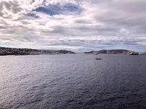 Ansicht der Insel von Mykonos Griechenland vom Meer Bewölkte Wolken im Himmel über der Insel lizenzfreie stockfotos