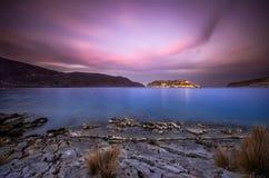Ansicht der Insel von Spinalonga bei Sonnenuntergang mit netten Wolken und ruhigem See Stockfotografie