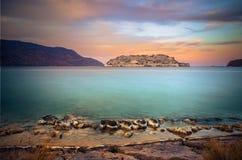 Ansicht der Insel von Spinalonga bei Sonnenuntergang mit netten Wolken und ruhigem See Lizenzfreie Stockfotos