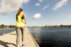 Ansicht der jungen Frau laufend auf Dock durch Fluss am Morgen Gesundheits-bewusstes Konzept lizenzfreie stockfotos