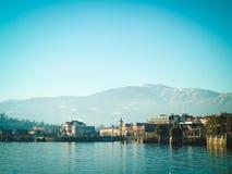 Ansicht der kleinen kursiven Stadt vom Damm Landschaft, Berge und See Lizenzfreie Stockfotografie
