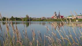 Ansicht der ländlichen Landschaft mit dem See und der Kirche Ruhiger Sommermorgen in Russland stock video footage