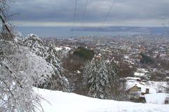 Ansicht der schneebedeckten Stadt vom Hügelrand Stockfoto