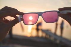 Ansicht der Sonne, des Meeres und des Himmels durch rosa Sonnenbrille Lizenzfreie Stockfotografie