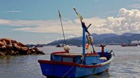 Ansicht der Stadt über Seebucht-nahem Fischerboot-bewölktem Himmel stock video