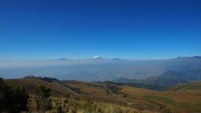 Ansicht der Stadt von Quito mit dem Cotopaxi-Vulkan im Hintergrund gesehen vom Rucu Pichincha Lizenzfreie Stockfotografie