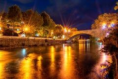 Ansicht der Steinbrücke über dem Fluss nachts mit mit Strahlen des Lichtes und der Reflexionen stockfotografie