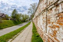 Ansicht der Straße von der langen alten Backsteinmauer Lizenzfreies Stockbild