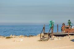 Ansicht der technologischen älteren Frau, die sunbath nimmt und ihren Handy auf Strandclub, Meer als Hintergrund, in Portugal ver lizenzfreie stockfotografie