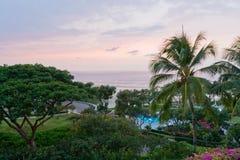 Ansicht der tropischen Rücksortierung des Ozeans mit üppigem Garten nach Sonnenuntergang. Lizenzfreies Stockfoto