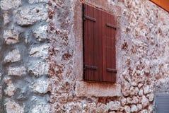 Ansicht der Wand des groben Steins und hölzernes Fenster des Abschlusses KONZENTRIEREN sich AUF C Stockfotografie