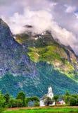 Ansicht der weißen hölzernen Kirche und Berge Oppstryn in Norwegen Lizenzfreie Stockbilder