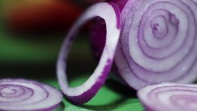 Ansicht der Zwiebel, die in Ringe mit scharfem Messer auf grünem Küchentisch gehackt wird stock video
