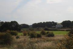 Ansicht des Bauernhofes über Ackerland Stockfotografie