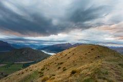Ansicht des Berges, des Sees und der drastischen Wolken bei Sonnenuntergang Lizenzfreies Stockbild