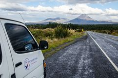 Ansicht des Bergs Ngauruhoe - Berg-Schicksal von der Straße in Nationalpark Tongariro mit weißem Autopackwagen im Vordergrund und lizenzfreies stockfoto