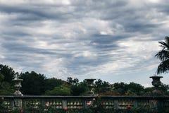 Ansicht des bewölkten Himmels des Parks mit einer Balustrade mit drei Blumentöpfen Stockfotografie