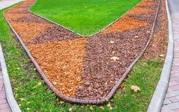 Ansicht des bunten orange und braunen Sägemehls im Blumenbeet und des grünen Rasens mit trockenem Herbstlaub Lizenzfreies Stockbild
