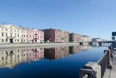 Ansicht des Dammes von Fontanka-Fluss mit Reflexionen von buildins im Wasser, St Petersburg, Russland Lizenzfreie Stockfotografie