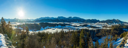 Ansicht des deutschen Dorfs und der Alpen im Winter Stockbilder