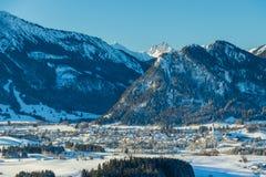 Ansicht des deutschen Dorfs und der Alpen im Winter Lizenzfreie Stockfotografie