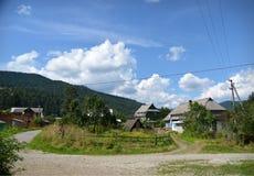 Ansicht des Dorfs auf einem Hintergrund von Bergen und von blauem Himmel Stockfotografie