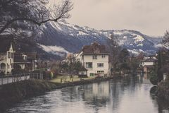 Ansicht des Dorfs mit Kanal- und Gebirgszughintergrund Stockbild