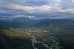Ansicht des Gebirgsflusses und des Dorfs von einer Höhe Sommer Stockfoto
