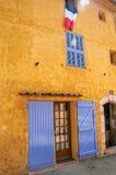 Ansicht des gelben Hauses mit Blauvorhängen und der Flagge in der Sillans-La-Kaskade Stockbild