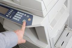 Ansicht des Geschäftsmannes den Knopf des Druckers im Büro drückend Lizenzfreie Stockbilder