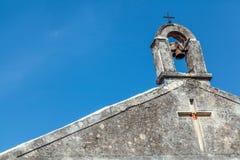 Ansicht des Glockenturms mit verrosteter Glocke und zwei Kreuzen Lizenzfreie Stockfotos