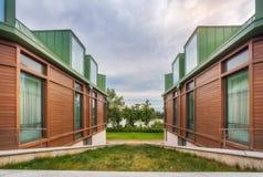 Ansicht des grünen Rasens zwischen Wänden und Fenstern des dreistöckigen hou Stockbild