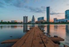 Ansicht des hölzernen Piers auf dem Stadtteich und den Wolkenkratzern von Yeka stockfotografie