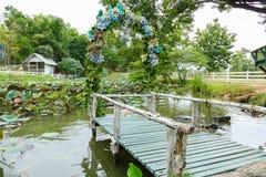Ansicht des hölzernen Piers, der mit blauem Blumen- und Wasserli verziert Lizenzfreies Stockfoto