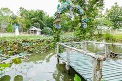 Ansicht des hölzernen Piers, der mit blauem Blumen- und Wasserli verziert Stockbild