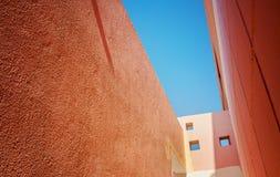 Ansicht des Himmels von einem schmalen Durchgang zwischen den orange Häusern Lizenzfreie Stockfotografie