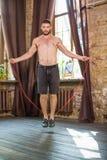 Ansicht des jungen athletischen Mannes, der mit Seil springt Stockbilder