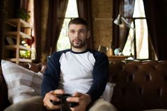 Ansicht des jungen Mannes sitzend auf der Couch, die Gamecontrollersteuerknüppel hält stockfoto
