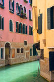 Ansicht des Kanals in Venedig mit rosafarbenem und gelbem Haus Stockfotografie
