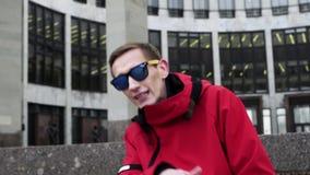Ansicht des lustigen Mannes in der roten Jacke und in der Sonnenbrille, die nahe bei Granitsäulen klopft stock footage
