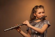 Ansicht des Mädchens mit dem langen Haar, das auf Flöte spielt Stockbilder