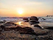 Ansicht des Meeres mit kleinen Wellen und felsigem Ufer, Sonnenaufgang reflektierte sich im Wasser Lizenzfreie Stockbilder